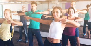 Men and ladies dancing zumba. Portrait of smiling young men and ladies dancing zumba at lesson Stock Images