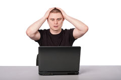 Men and laptop. Man sits with a laptop grabbed his head Stock Photography