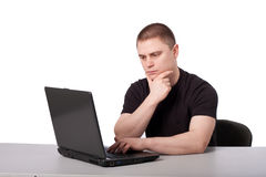Men and laptop. Man sits thoughtfully with a laptop leaning on the arm Stock Photo