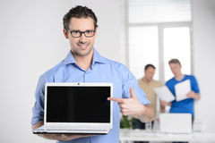 Men with laptop. Happy young businessman holding a laptop and po Royalty Free Stock Images