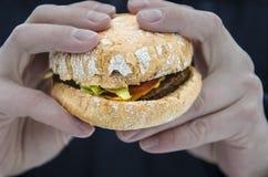 Men& x27; las manos de s guardan una hamburguesa jugosa fresca con el tomate imagen de archivo