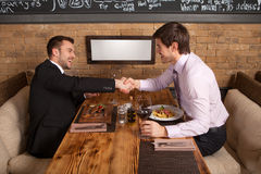 Men laugh together while sitting in cafe. Stock Images