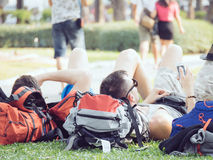 Men laying down on the grass play mobile phone Royalty Free Stock Photography