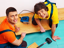Men laying parquet at home Stock Photos