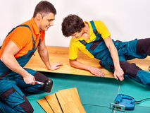 Men laying parquet at home Stock Images
