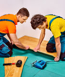 Men laying parquet at home Royalty Free Stock Image