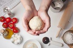 Men& x27; le mani di s tengono la palla di pasta per pizza su una tavola e sugli ingredienti Fotografie Stock Libere da Diritti