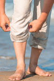 Men legs in linen trousers. On background of the sea Stock Photography