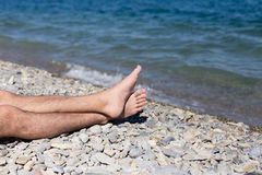 Men legs on a pebble beach by the sea Royalty Free Stock Photography