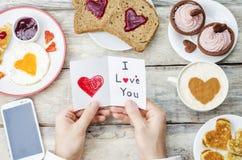 Men& x27 ; les mains de s tiennent une carte de valentines de salutation Photographie stock libre de droits