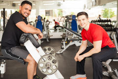 Men lifting some weights at the gym. Portrait of two young Hispanic men taking a break and talking between sets while lifting weights at the gym Stock Photos