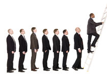 Men in line. Group of men standing in a line, waiting to climb a ladder stock image