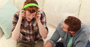 Men listening music on a sofa stock video footage