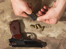 Men load ammo in the clip Makarov pistol. Soldier load ammo in the clip Makarov pistol. Close up Royalty Free Stock Photography