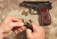 Men load ammo in the clip Makarov pistol Stock Images