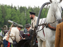 Men load machine gun on cart. RUSSIA, CHERNOGOLOVKA - MAY 17: Unidentified men load machine gun on cart on History reenactment of battle of Civil War in 1914 Royalty Free Stock Photography
