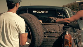 Men loaded tires from the car. White men loaded tires from the car in hot summer day stock video footage