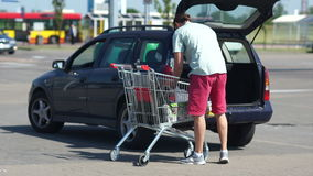 A men loading foods from shopping cart into car trunk at parking lot. The role of men in the family. Distribution of stock video