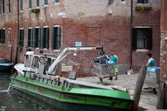 Men loading trash on garbage boat, Venice Royalty Free Stock Photo