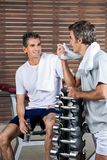 Men Looking At Each Other After Work Out. Happy men looking at each other after work out in health club Royalty Free Stock Images