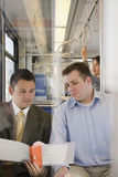 Men looking at file on train royalty free stock photography