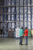 Men Looking At Full Warehouse Shelves Royalty Free Stock Images
