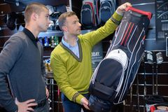 Men looking at golf club bag in sports shop. Sport royalty free stock photo