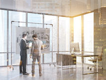 Men looking at papers in office,. Rear view of two businessmen wearing suits. They are standing near a whiteboard and looking at papers. Office. 3d rendering Royalty Free Stock Photography