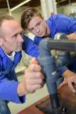 Men looking at pipework and gauge. Man stock photos