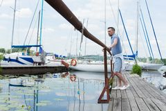 Men looking into river water at pier barrier. Man walking on river pier near of boats. Guy Standing by the Dock. Men looking into river water at pier barrier stock photo