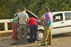 Men looking under the hood and repairing broken down Fiat car in the Valle de Vi�ales, in central Cuba Stock Image