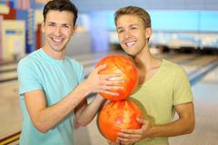 Men make column from balls in bowling club Stock Photos