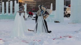 Men make ice sculptures for Ice town stock video footage
