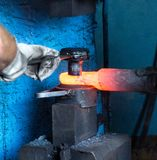 Men make a metal red-hot detail in an old smithy, close-up, red-hot meta, forging royalty free stock photos
