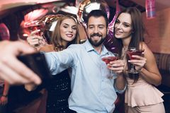 A man makes selfie with his friends. He has fun in a nightclub. Against the background stand his friends with cocktails. A men makes selfie with his friends. He Royalty Free Stock Image