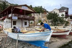 Men making repairs to a fishing boat in the Mediterranean coastal town of Kalekoy in Turkey. Royalty Free Stock Photography