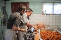 Men making sausages the traditional way using sausage filler. Stock Image