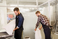 Men with malt bags and mill at craft beer brewery. Manufacture, business and people concept - men with bags weighing and pouring malt to mill at craft brewery or Stock Photography