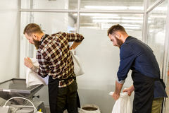Men with malt bags and mill at craft beer brewery. Manufacture, business and people concept - men with bags weighing and pouring malt to mill at craft brewery or Royalty Free Stock Photography