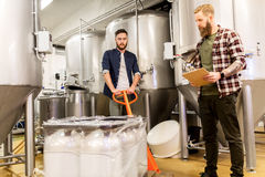 Men with malt and clipboard at craft beer brewery. Manufacture, business and people concept - men with malt bags on loader and clipboard working at craft brewery stock photography