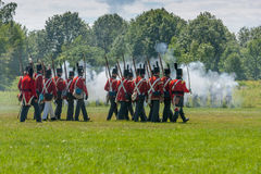 Men Marching in Field during Reenactment. MORRISBURG, CANADA - JULY 14: Men marching across a field during the Battle of Crysler's Farm reenactment on July 14 Stock Photo