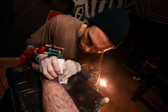 A man master fills a tattoo to a young man. Tattoo parlor. Drawing on skin royalty free stock photography