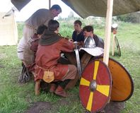 Men medieval warriors in knight`s armor resting on a halt after the battle on the traditional annual holiday in Russia Kolyvan 201 stock photo