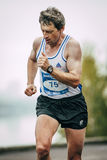 Men middle-aged runner runs along river Royalty Free Stock Images