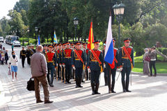 Men in military uniform stand holding flags. Royalty Free Stock Images