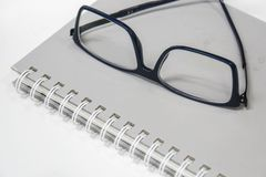 Men minimal eye glasses on notebook for reading and writing in office. Men modern minimal eye glasses on notebook for reading and writing in office stock photography