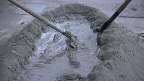 Men mixing blend of water and sand. Wide angle shoot of two men spinning and mixing sand with water and preparing a concrete for building a house stock footage