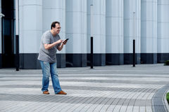 Men with a mobile phone in front of a white business center look Royalty Free Stock Photography