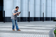 Men with a mobile phone in front of a white business center look Royalty Free Stock Photos