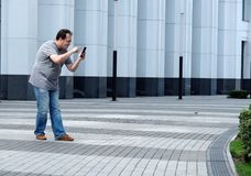 Men with a mobile phone in front of a white business center look Stock Photos